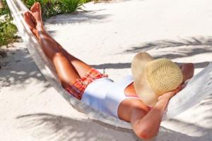 Woman relaxing in the hammock between palm trees, Fotolia.de